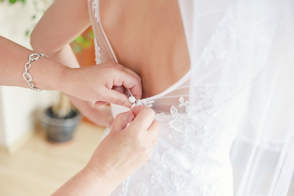 Closing the button of a wedding gown