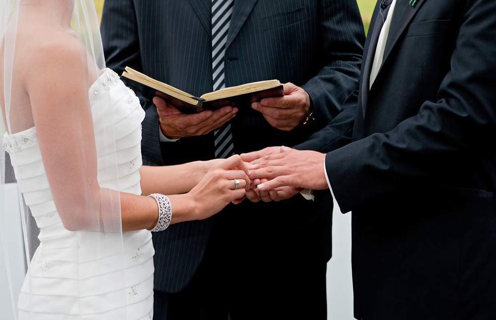 Bride putting wedding ring on groom