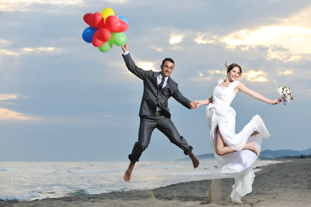 Bride and groom jumping in the beach with balloons