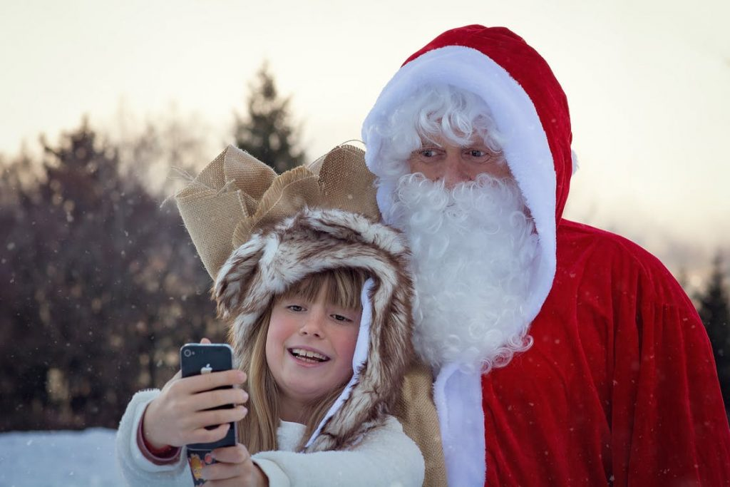 Little girl taking a selfie with Santa